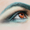 62417156 - male eye with dark eyeshadow black eyebrow makeup and decorative orange contact lens and blond hair closeup